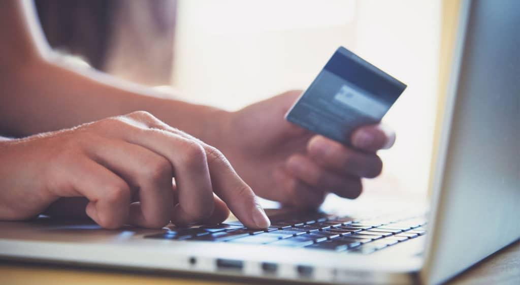 Mains tenant carte de crédit et utilisant un ordinateur portable